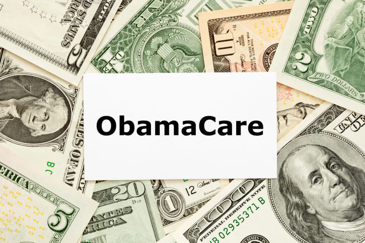 word obamacare on paper on top of currency