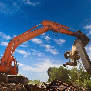 front end loader demolishing a house