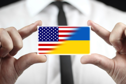 Businessman holding a business card with Ukraine and USA Flag