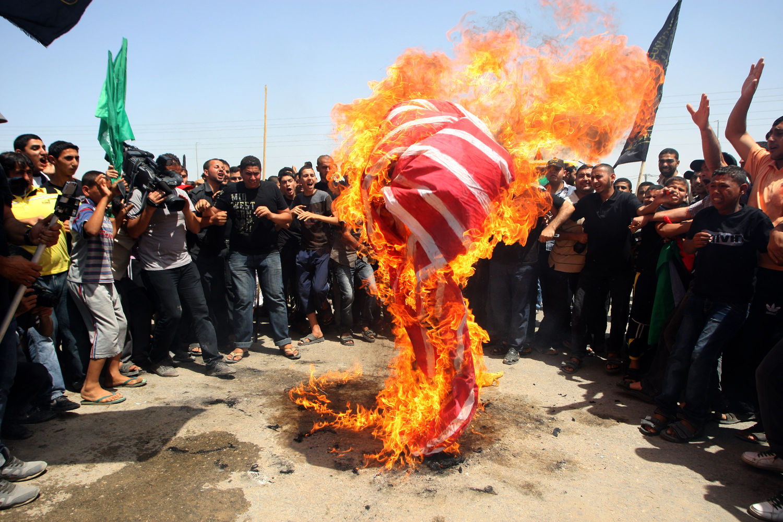 Palestinians burn an American flag