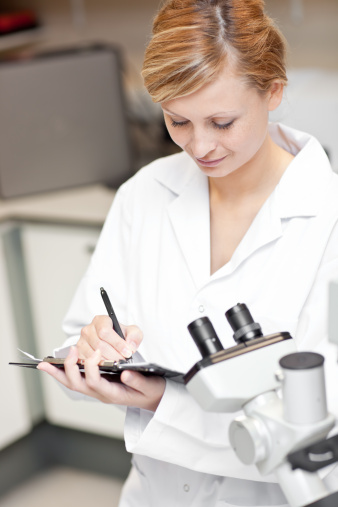 Concentrated female scientist writing on her clipboard