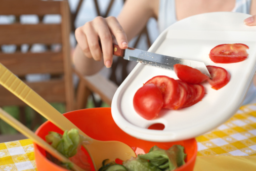 Woman putting sliced tomatoes into salad
