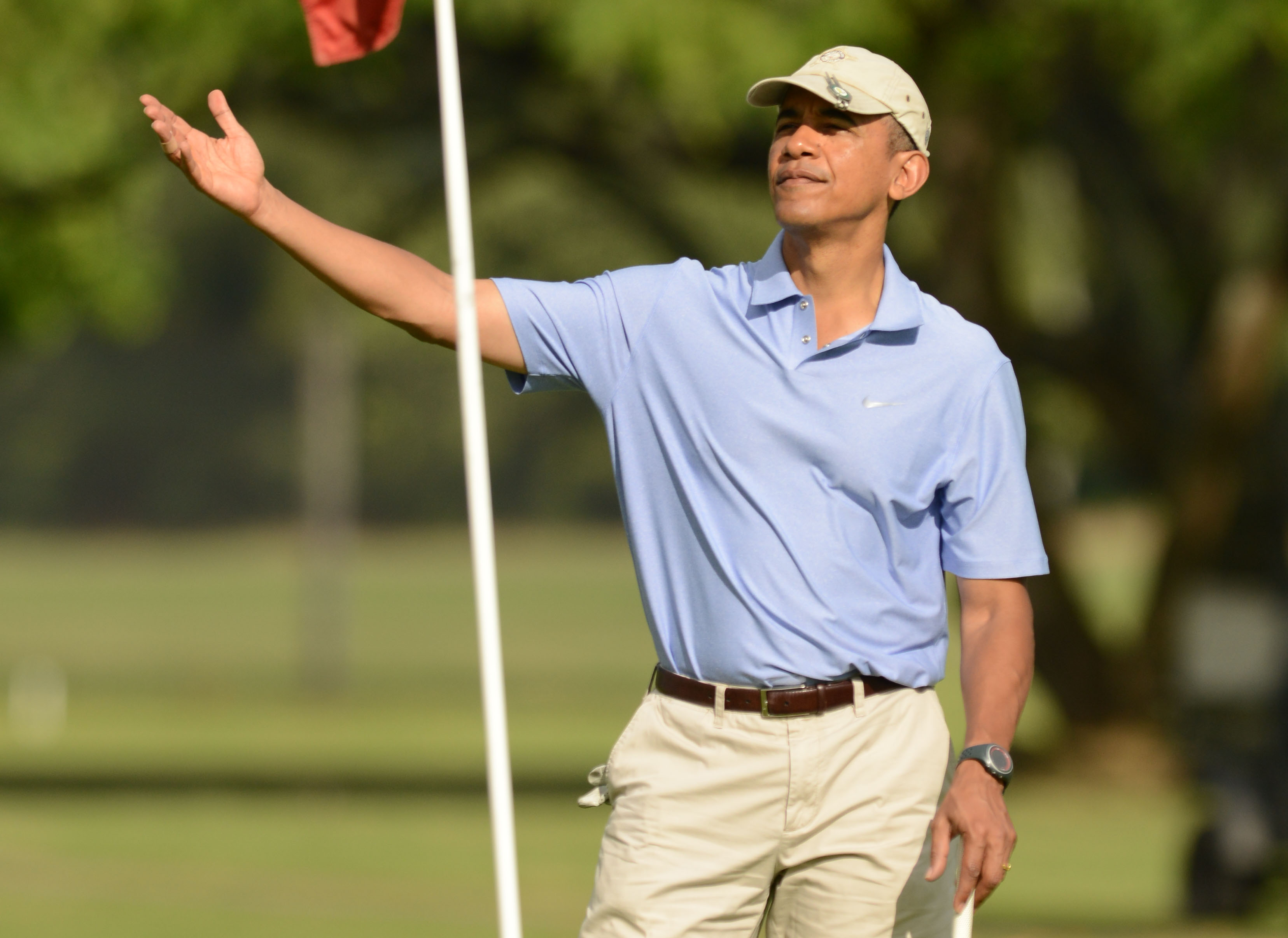 President Barack Obama reacts on the 2nd green while golfing with the Prime Minister of New Zealand John Key, at Marine Corps Base Hawaii's Kaneohe Klipper Golf Course, Kaneohe, Hawaii, January 2, 2014. President Obama played a round of golf with Prime Minister of New Zealand John Key, the Prime Ministers son Max Key and White House aide Marvin Nicholson. UPI/Cory Lum