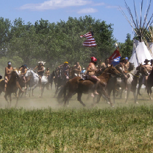 During a reenactment of the Battle of the Little Bighorn, known as Custer's Last Stand, smoke swirled among the teepees as guns were fired by U.S. 7th Cavalry soldiers at the Arapahoe, Cheyenne and Lakota Indians.