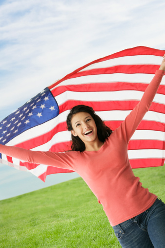 Hispanic teenaged girl holding American flag