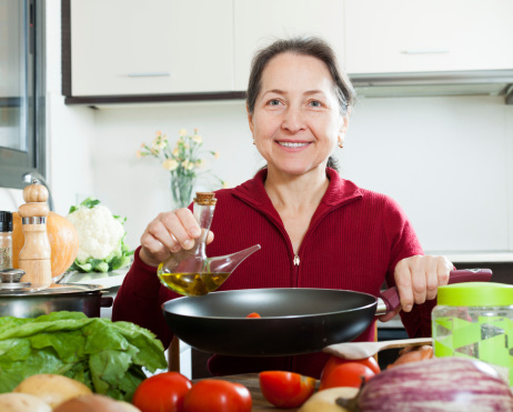 Happy mature woman pouring oil into skillet