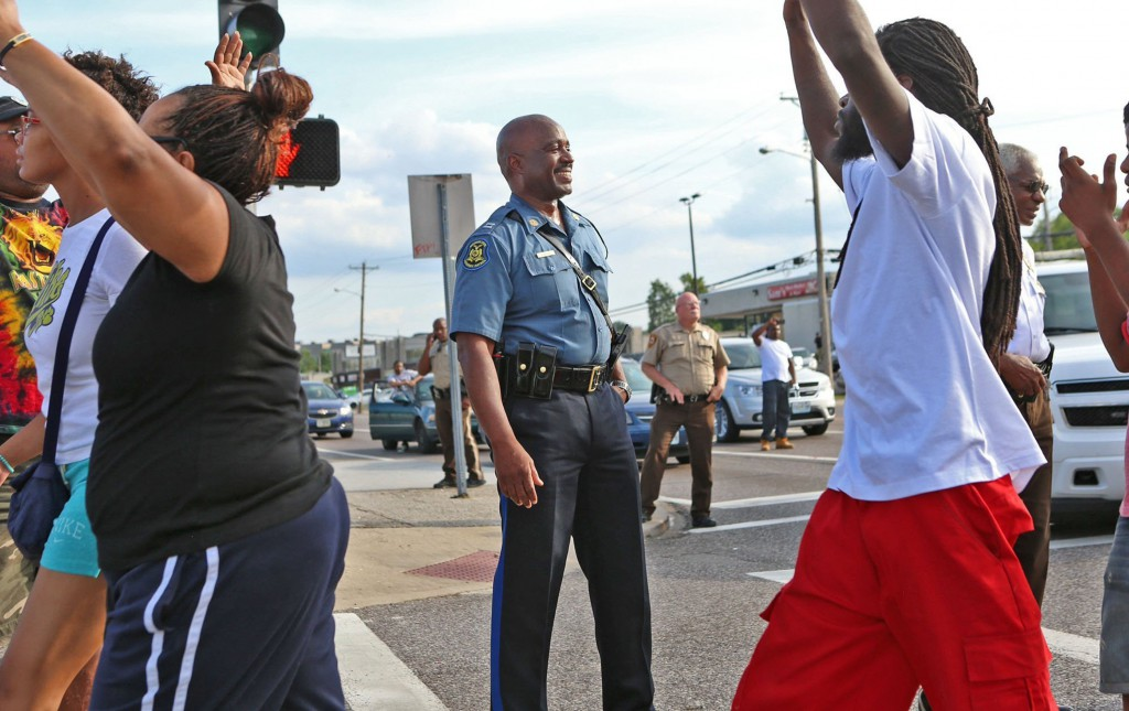 Capt. Ronald Johnson of the Missouri Highway Patrol smiles at demonstrators marching along W. Florissant Avenue in Ferguson on Thursday, Aug. 14, 2014. (David Carson/St. Louis Post-Dispatch/MCT)