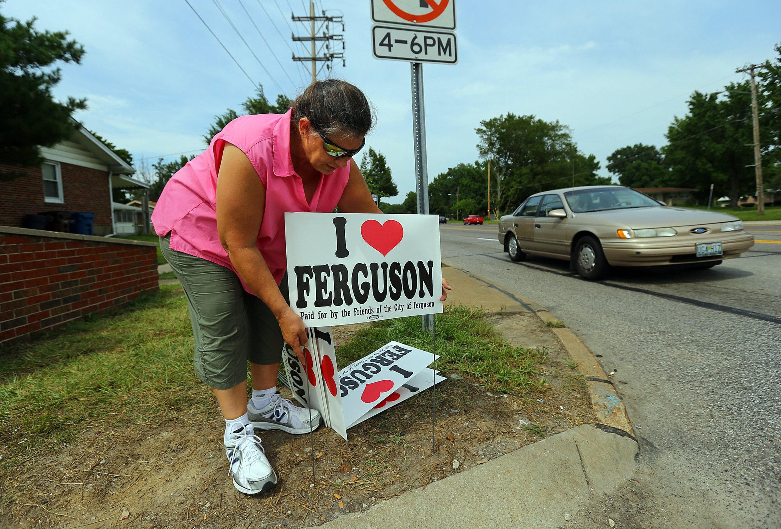 "Rainey Wilson, who lives in Ferguson, sets out signs along West Florissant Avenue on Wednesday, August 20, 2014, in Ferguson, Mo. ""We love Ferguson and want everyone to know it's not a bad place,"" said Wilson. (Curtis Compton/Atlanta Journal-Constitution/MCT)"