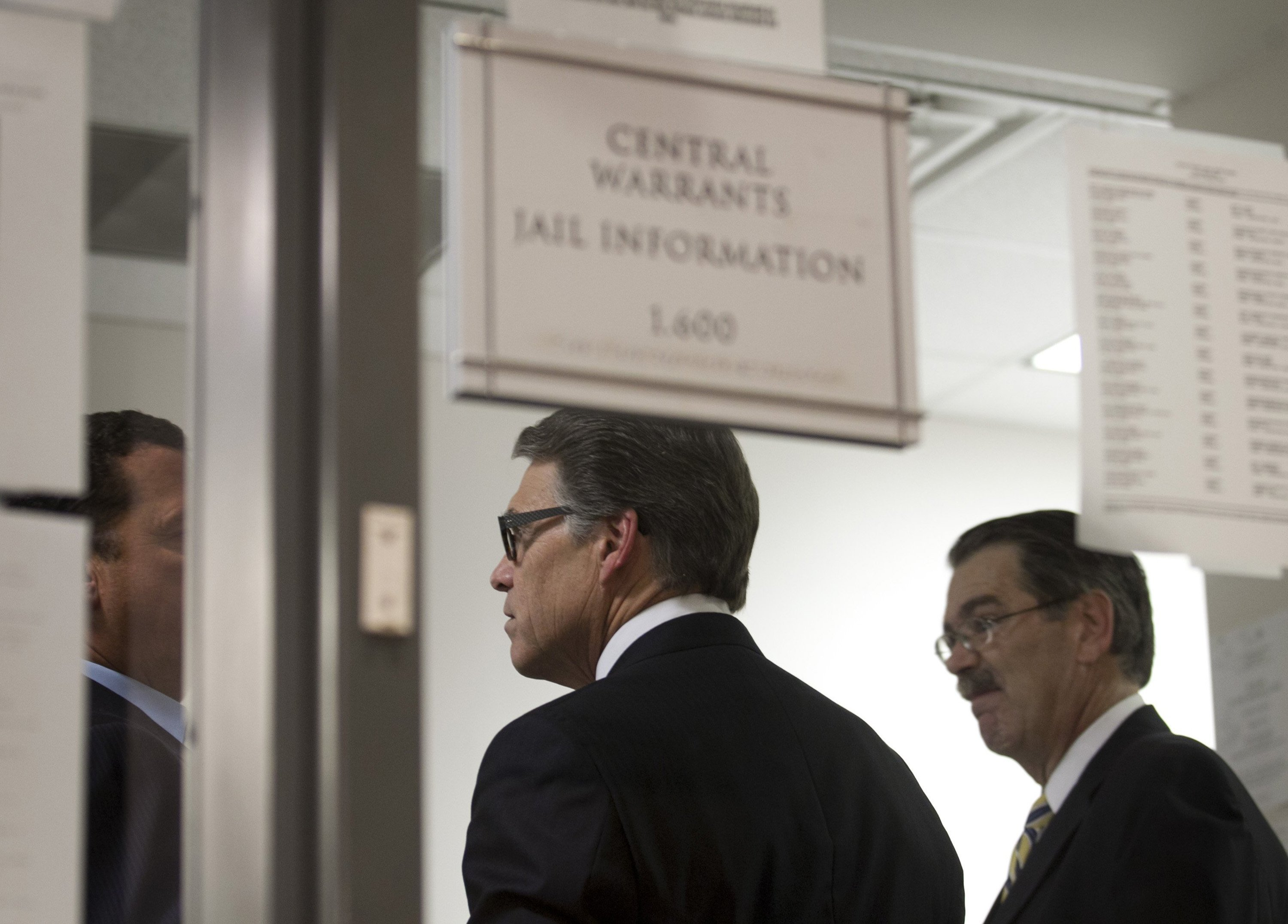 Texas Gov. Rick Perry, middle, is booked at the Blackwell-Thurman Criminal Justice Center in Austin, Texas, for two felony indictments of abuse of power on Tuesday August 19, 2014. (Jay Janner/Austin American-Statesman/MCT)