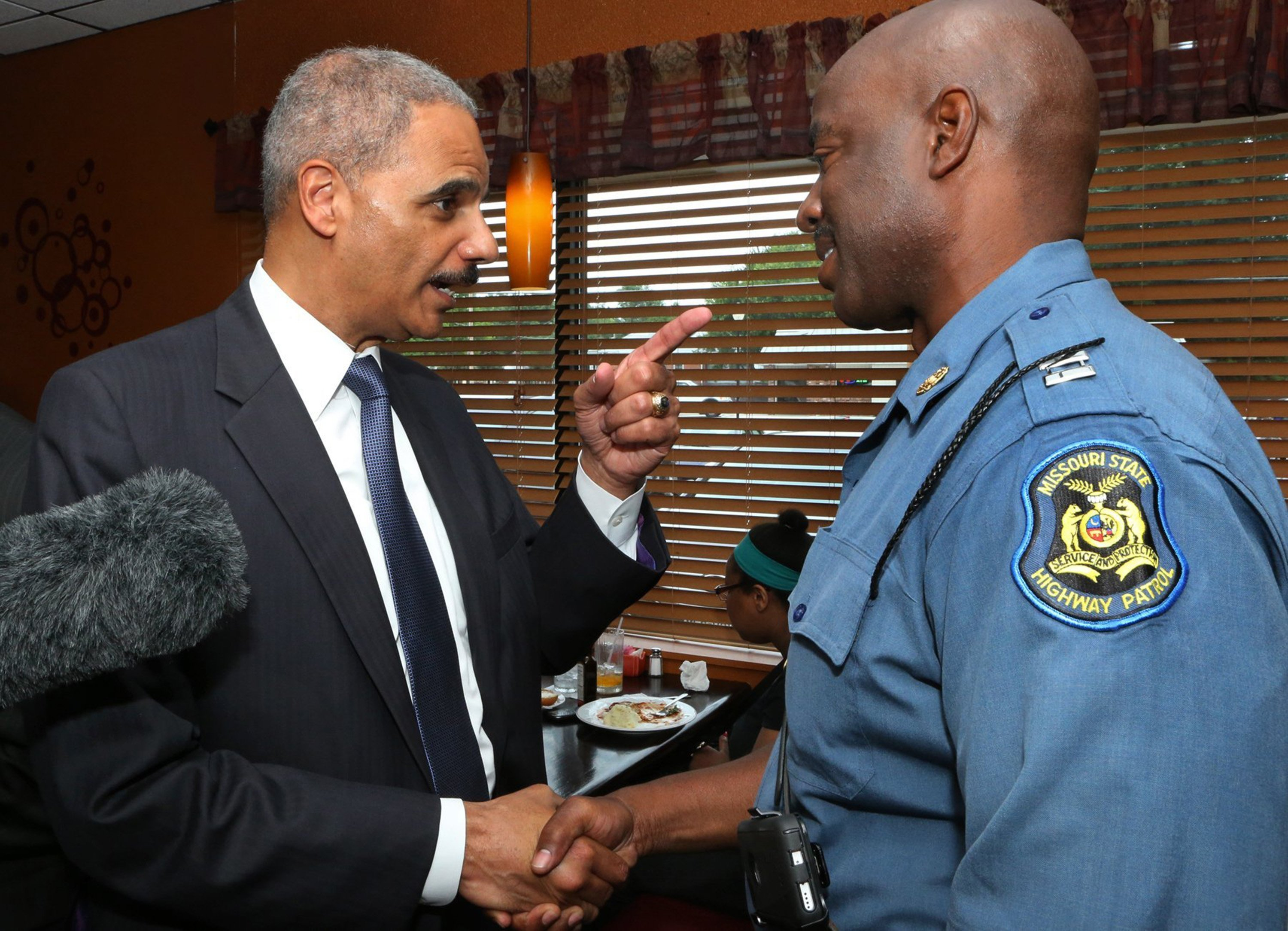 Attorney General Eric Holder tells Missouri Highway Patrol Capt. Ron Johnson that he needs to be sure to get some sleep and to not forget to tell his wife happy anniversary on Wednesday, Aug. 20, 2014, at Drake's Place Restaurant in Ferguson, Mo. Wednesday was the 26th wedding anniversary for Capt. Johnson. (J.B. Forbes/St. Louis Post-Dispatch/MCT)