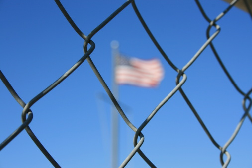 border illustration american flag seen through chain link fence