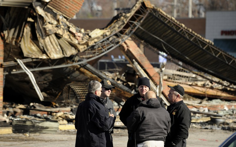 Police investigators meet in front of a burned strip mall at Chambers Road and West Florissant Avenue in Ferguson on Tuesday, Nov. 25, 2014. (Wally Skalij/Los Angeles Times/TNS)