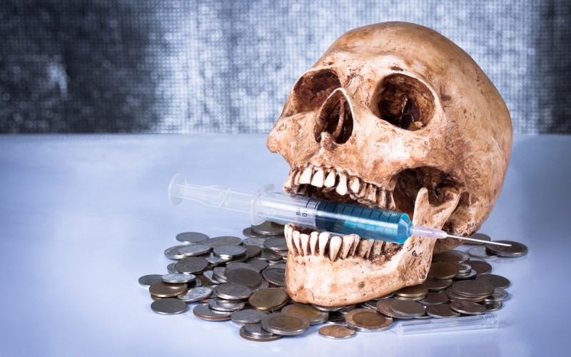 skull with syringe in mouth