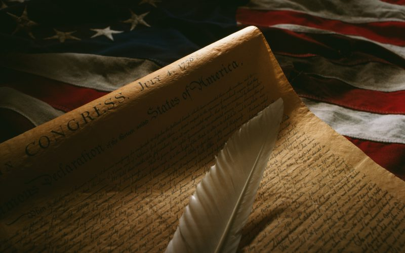 Declaration of Independence on original US flag with quill in foreground